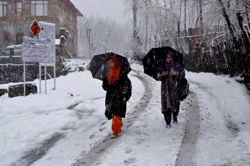 Kashmiri Women hold umbrellas as they walk on a snow covered road during a heavy snowfall in the valley, at Qazigund,